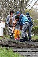 変形して段差の出来た道を避難する親子=16日午後4時17分、熊本県南阿蘇村、遠藤啓生撮影
