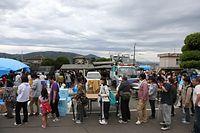 傘を持って炊き出しの列に並ぶ被災者たち=16日午後5時24分、熊本県益城町、上田幸一撮影