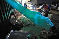満員の避難場所に入れず、軒下にブルーシートで屋根をつくって過ごす老人ホームからの避難者ら=16日午後7時38分、熊本県益城町、内田光撮影