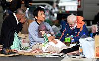 避難所の軒下にシートを広げて座る人たち=16日午後5時24分、熊本県益城町、内田光撮影