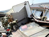 崩壊した住宅を一軒一軒回り、行方不明者が残っていないか調べる自衛隊員ら=16日午後2時12分、熊本県南阿蘇村、西畑志朗撮影
