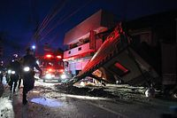 地震で倒壊した建物の脇を通って警察官らが救助捜索活動に向かった=16日午前5時4分、熊本県益城町、小宮路勝撮影