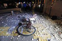 歩道には外壁がはがれ落ち、自転車が倒れていた=16日午前3時12分、熊本市中央区、金子淳撮影