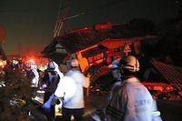 倒壊した建物の脇を通って、警察官らが救助捜索活動に向かった=16日午前3時28分、熊本県益城町、小宮路勝撮影