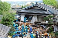 倒壊した民家に取り残された人を捜す警察の救助隊=16日午前6時44分、熊本県西原村、上田幸一撮影