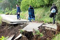 崩落した道路を慎重に歩く人たち=16日午前6時25分、熊本県西原村、上田幸一撮影