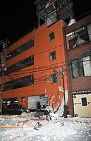 熊本市の繁華街では立体駐車場の外壁などが崩れ、道路をふさいだ=16日午前3時36分、熊本市中央区、小野大輔撮影