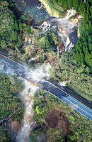 土砂崩れ現場では大量の水が道路上に流れ、滝のようになっていた=16日午前6時27分、熊本県南阿蘇村、朝日新聞社ヘリから、高橋雄大撮影