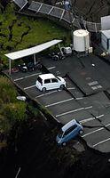 土砂が崩れた駐車場に残った車=16日午前6時30分、熊本県南阿蘇村、朝日新聞社ヘリから、高橋雄大撮影