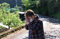 倒壊した民家に取り残された女性が遺体となって発見されたと聞き、手を合わせる近隣に住む女性。「昨日、会ったのに」と信じられない様子だった=16日午前8時56分、熊本県西原村、上田幸一撮影