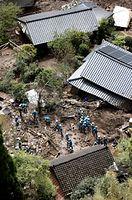 土砂崩れ現場で捜索する警察官ら=16日午前11時11分、熊本県南阿蘇村、朝日新聞社ヘリから、高橋雄大撮影