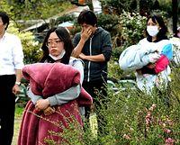 1階がつぶれたアパートで行方不明者の捜索を見守る学生たち=16日午後3時27分、熊本県南阿蘇村河陽の竹原アパート、長沢幹城撮影