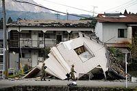 地震で倒壊した建物周辺を歩く自衛隊員=16日午後3時45分、熊本県南阿蘇村、長沢幹城撮影