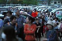避難所の炊き出しに並ぶ人たち。男性は、「2時間並んで50メートル進んだだけ」と疲れた様子だった=16日午後6時59分、熊本県益城町の広安小学校、金川雄策撮影