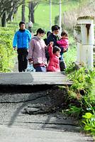 避難所で一夜を明かした住民らは、生活に必要な物を探そうと亀裂や段差のある道を歩いて自宅へ向かっていた=17日午前8時すぎ、熊本県南阿蘇村、長沢幹城撮影