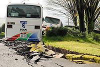 東海大学のキャンパス内の道路には亀裂が走り、バスがはまりこんでいた=17日午前8時17分、熊本県南阿蘇村、長沢幹城撮影