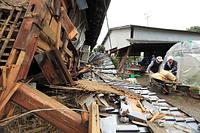 倒壊した自宅に戻り米を運び出す今吉出己(いずみ)さん(77)と妻のカシコさん(78)。「1年分の食料ですから。ダメになったら大変です」=17日午前10時3分、熊本県益城町寺迫、内田光撮影