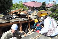 崩れた家の屋根に穴を開け、部屋の中から物を取り出す住民。周りの家も傾いたままだった=17日午前、熊本県益城町、白井伸洋撮影
