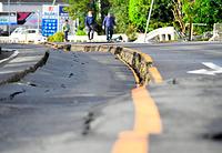 アスファルトが大きくひびわれた道路=17日午前7時19分、熊本県益城町、白井伸洋撮影