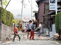 地震で出来た道路のひび割れを直そうと、がれきを敷いて踏み固める子供たち=17日午前10時42分、熊本県益城町、森井英二郎撮影