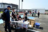 熊本空港の駐車場に臨時にできた搭乗受付カウンター(手前)。左奥はターミナルビル、右奥は手荷物検査場=19日午後2時43分、熊本県益城町、水野義則撮影
