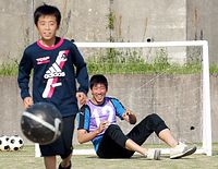 避難生活を送る小中学生向けに「サッカー教室」を開いたロアッソ熊本の畑実さん(奥)=19日午後4時11分、熊本県益城町田原、小宮路勝撮影