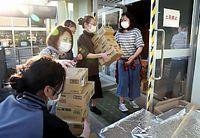 届いた物資を校舎に運ぶ避難者ら=19日午後5時38分、熊本市中央区の西山中学校、細川卓撮影