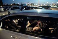 熊本県益城町の大型展示場「グランメッセ熊本」の駐車場で車中泊をする北嶋博文さん。余震が心配なので熊本市内の自宅を離れて、家族とここで寝泊まりしているという=19日午後7時26分、加藤諒撮影