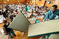 避難所の広安西小学校で畳を配るボランティア。体育館に配布の放送が流れると行列が出来た=19日午前9時50分、熊本県益城町、小宮路勝撮影