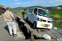 ガス復旧のために被災地を走行していた軽自動車が大きく傾き、ひび割れた道路に行く手を阻まれていた=17日午後3時49分、熊本県益城町、加藤諒撮影