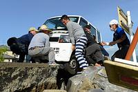 ガス復旧のために被災地を走行していた軽自動車が、アスファルトの割れ目にタイヤを落としてしまい動けなくなった。近くにいた男性が「誰か来いや!」と叫ぶと、ボランティアで民家の片付けのため鹿児島から来ていた