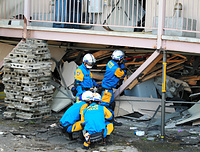 1階部分が潰れたアパートで、棒の先端に付いているカメラで行方不明者がいないか捜索する愛知県警広域緊急援助隊=17日午後4時27分、熊本県益城町、内田光撮影
