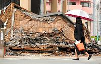 倒壊した洋食屋の前を通って出勤する女性=17日午後9時57分、熊本市中央区、細川卓撮影