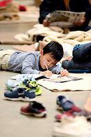 避難所の小学校の廊下で、絵を描いて過ごす子ども=18日午前9時34分、熊本市中央区の慶徳小学校、細川卓撮影