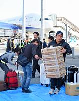 熊本空港再開後に着陸した一番機から、生活物資などの荷物を受け取る乗客たち=19日午前7時54分、熊本県益城町、森井英二郎撮影