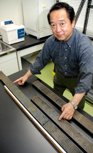 写真:2千年前の巨大津波の痕跡を発見した岡村真教授。ボーリング試料(左)で岡村教授が両手で示す範囲がその跡=高知市、川原写す
