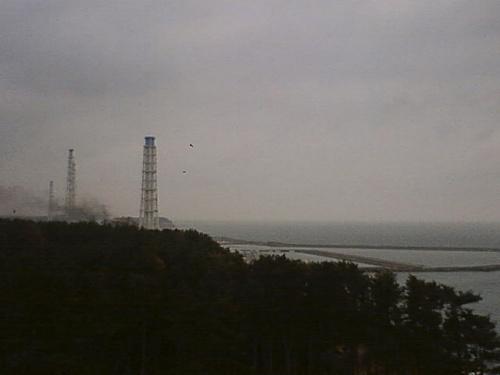 写真:15日午前7時、固定カメラで撮影された福島第一原発。建物(左側)から煙が上がっている=ロイター