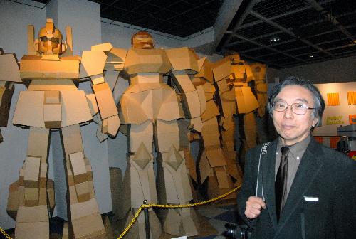 写真:小川進さんと展示されている段ボールのロボット=福岡県久留米市