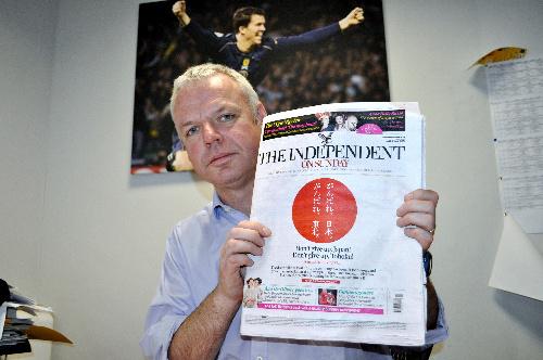写真:「がんばれ、日本」の紙面を手にするジョン・マリン編集長=ロンドン、橋本写す