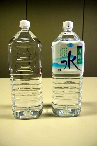 写真:日本生活協同組合連合会が被災地向けに製造するラベルなしのペットボトル飲料水(左)と、通常時のラベルをはった商品=日本生協連提供