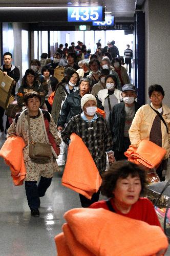 写真:福島県川俣町の避難所から「さいたまスーパーアリーナ」に到着した双葉町の住民たち=19日午後3時14分、さいたま市中央区、遠藤啓生撮影
