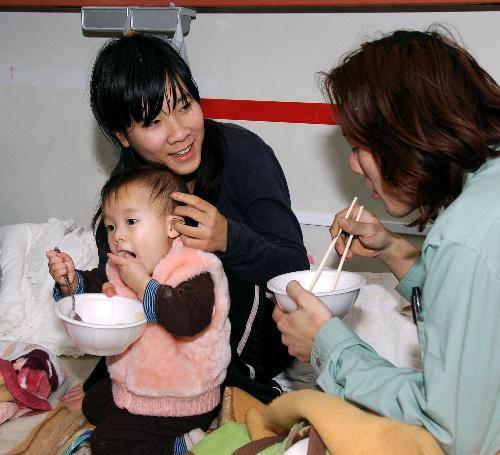 写真:避難所の教室で、炊き出しで出されたご飯とみそ汁を食べる(右から)松坂雄基さん、翔子さん、優菜ちゃん一家=宮城県石巻市、千葉写す
