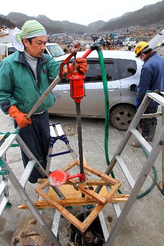 写真:使えなくなった給油所の地下タンクから、手押しポンプでガソリンがくみ上げられた=20日、岩手県大槌町、樫山晃生撮影