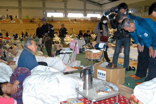 写真:避難所を訪問し、住民に謝罪する皷紀男・東京電力副社長(右)=22日午後3時、福島県田村市、下地写す