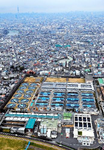 写真:乳児の飲用に適さない濃度の放射性ヨウ素が検出された東京都水道局の金町浄水場。後方は東京都心=23日午後2時54分、東京都葛飾区、朝日新聞社ヘリから、仙波理撮影