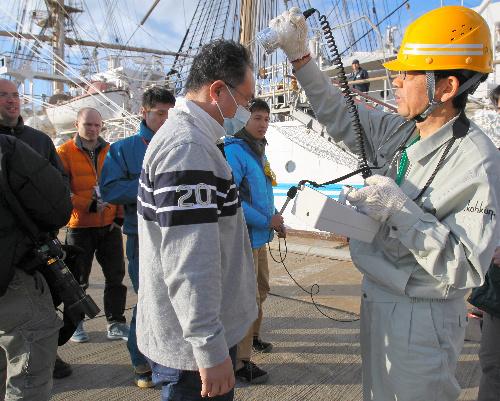 写真:福島第一原発の復旧作業から休憩に戻り、線量計の測定を受ける東京電力の作業員=23日、福島県いわき市の小名浜港、河合博司撮影