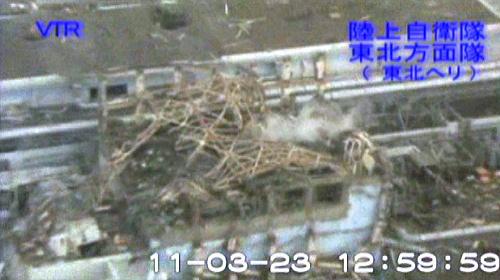 写真:白煙があがる福島第一原発3号機の原子炉建屋(手前)=23日、陸上自衛隊提供