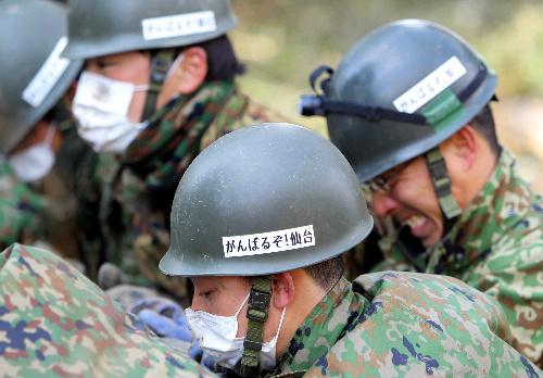 写真:仙台市宮城野区で作業に当たる自衛隊員のヘルメットには「がんばるぞ!仙台」と書かれたシールが貼られていた=26日午後、長島一浩撮影
