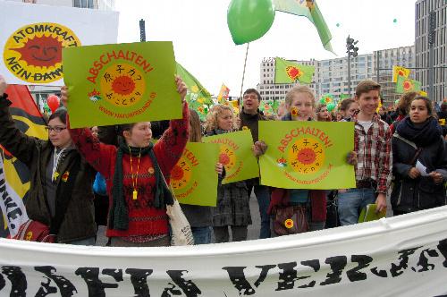 写真:日本語で「原子力? おことわり」と書かれたポスターを持ってデモ行進する参加者たち=ベルリン、松井健撮影