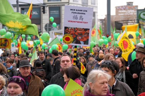 写真:「誰が福島の責任をとることができるのか」と書いたプラカードを持ってデモ行進する参加者=ベルリン、松井健撮影